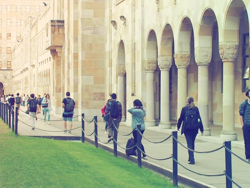 people walking in front of sandstone university buildings