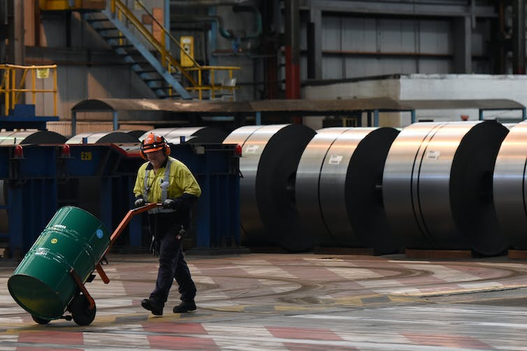 workers walk past rolls of finished steel