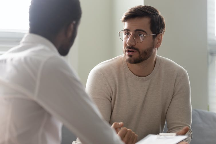 A young man talks with a clinician.