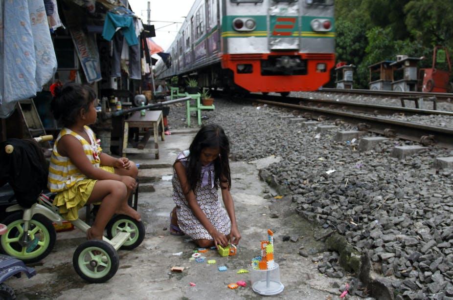 Dua orang anak bermain di pinggir rel kereta api.
