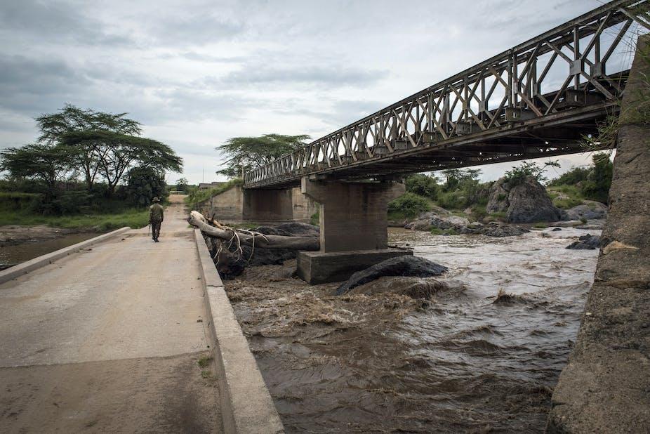 A man walks on a concrete road bridge over a river, next to a higher steel railway bridge