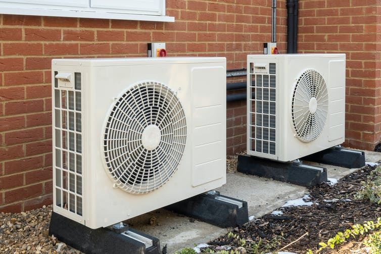 Two large white units with central fans outside a house.