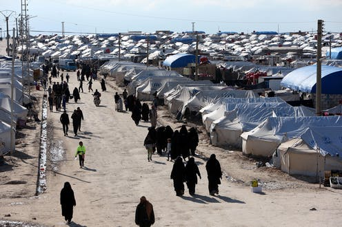 A long view of the al-Hol displacement camp in Syria, where people are walking between tents.