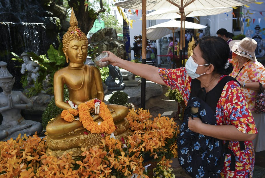 A woman pours scented water on a Buddha statue at Wat Pho temple in Bangkok, Thailand.