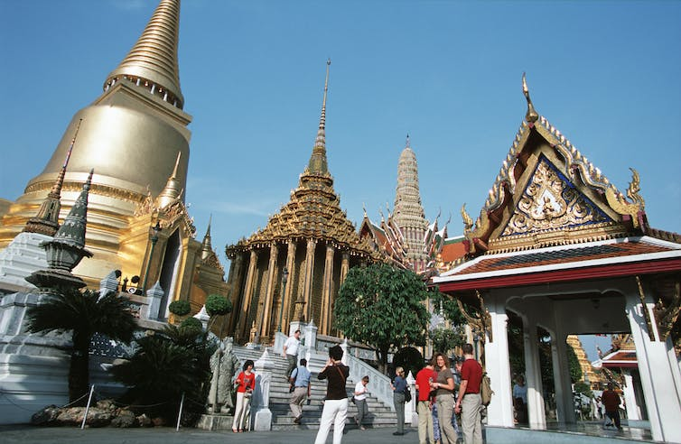 Visitors enjoy the magnificent views of Wat Phra Kaew, temple of the emerald buddha, which is situated in Bangkok's Grand Palace