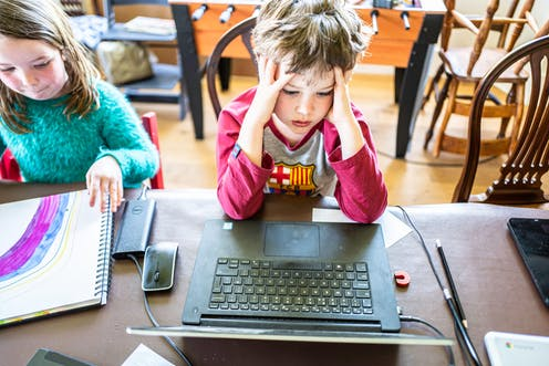 A little boy in a red t-shirt holds his head in his hands as he does an online school lesson from home with his sister