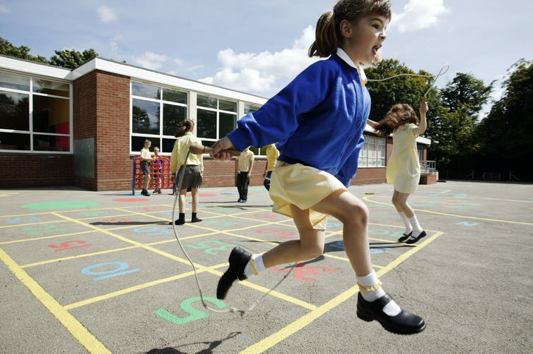 A primary school girl skips in the playground