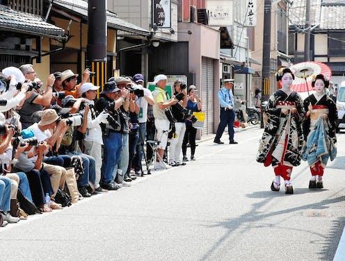 Des touristes agglutinés photographient deux geishas qui marchent sur la rue.