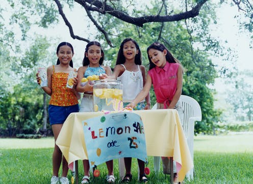 four young girls outside standing behind a table selling lemonade for 25 cents