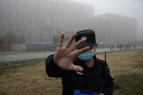 Security guard raises his hand to prevent people from entering the security perimeter of the Wuhan Institute of Virology (WIV)