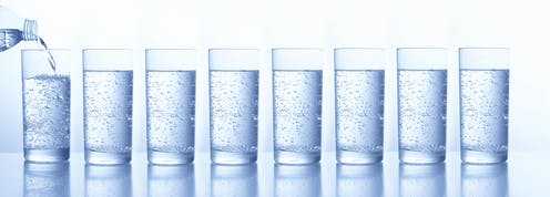 A line of glasses filled with water.