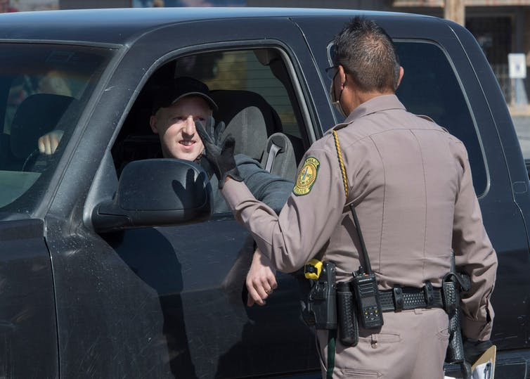 A police officer talks to a man driving a vehicle