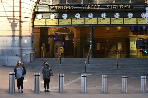 Two people wearing masks standing outside Flinders Street Station in Melbourne, Victoria