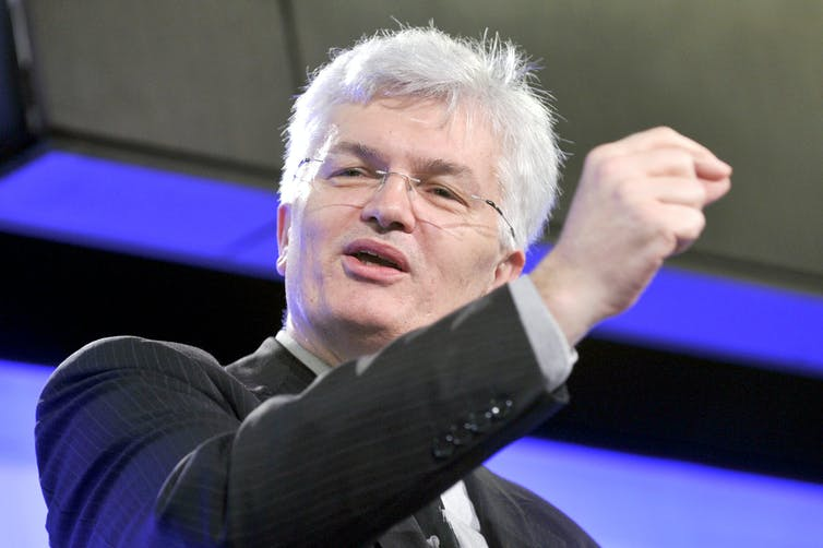 Man in suit gestures during a speech