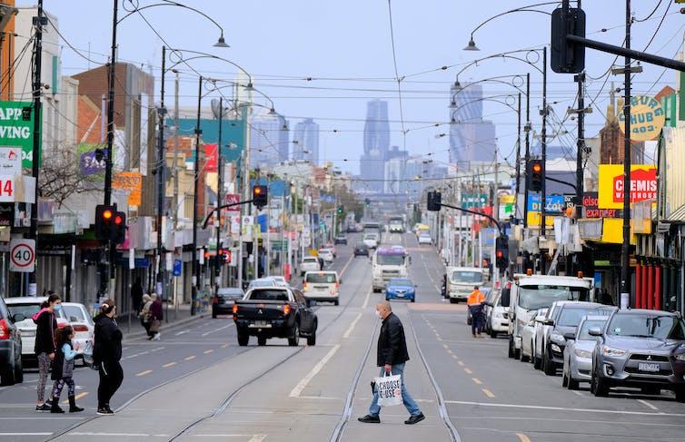 Pedestrians cross Sydney Road in Melbourne's Coburg during lockdown.