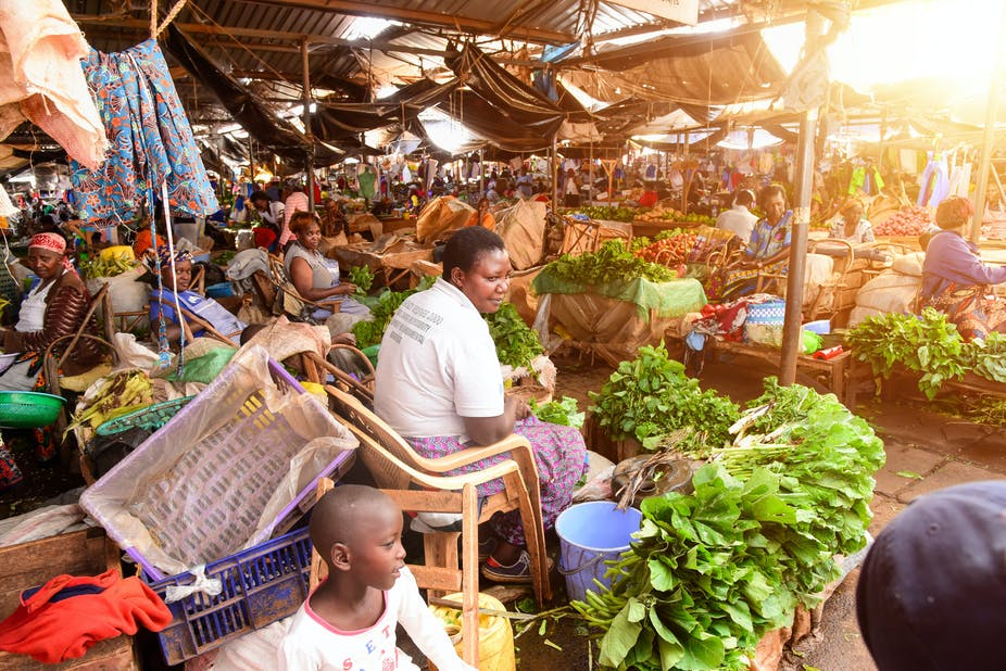 Vendors sell fruits and vegetables at an informal food market.