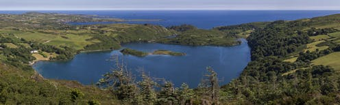 A large blue lake surrounded by green hills and the ocean beyond.