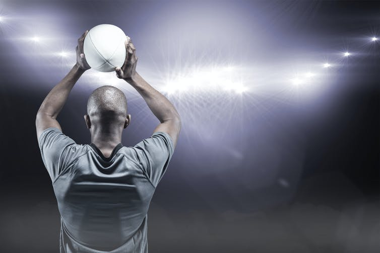 Back of man facing stadium lights and holding rugby ball over his head