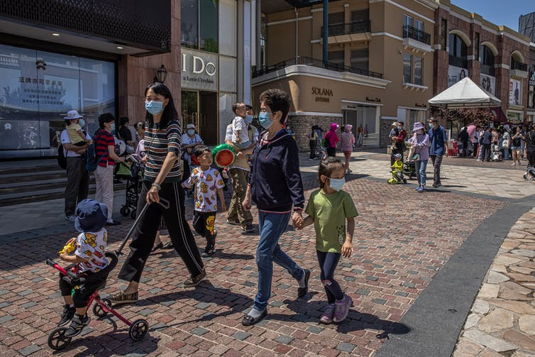 A woman pushes a child on a stroller, while walking beside an older woman holding the hand of a young girl. They are walking past shops at an outdoor shopping mall.