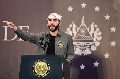 Bukele, wearing his signature backwards baseball cap, stands at a lectern and points