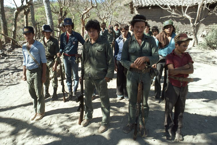 Young people, some in fatigues carrying weapons, stand in formation