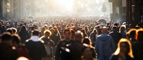Une foule anonyme se déplaçant dans la rue.