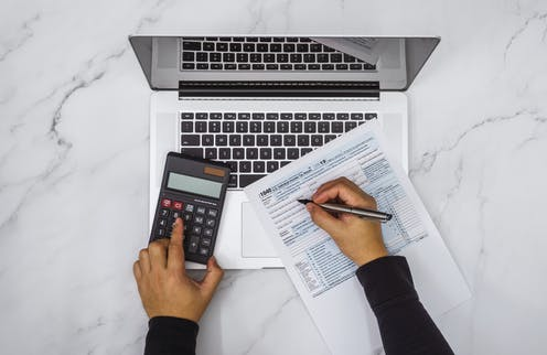 Someone's left hand is holding a calculator while the right hand is holding a pen on a 1040 form, atop a laptop