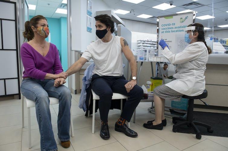 Justin Trudeau reçoit une dose de vaccin tandis que sa femme Sophie Grégoire Trudeau tient sa main