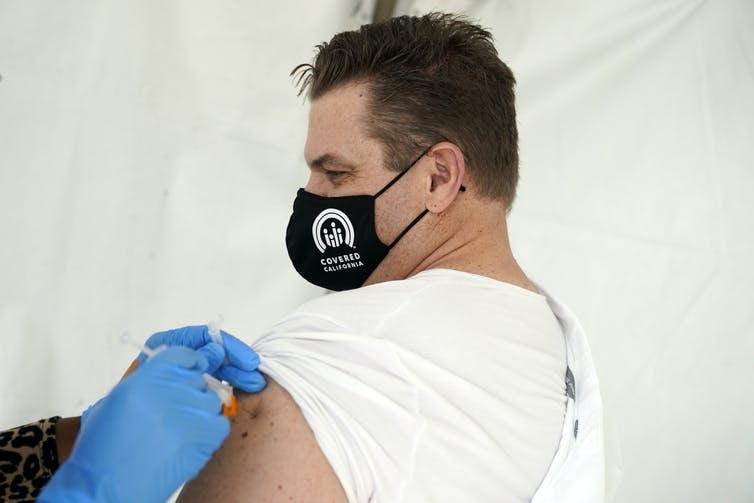 A man wearing a mask getting his COVID-19 vaccine shot.