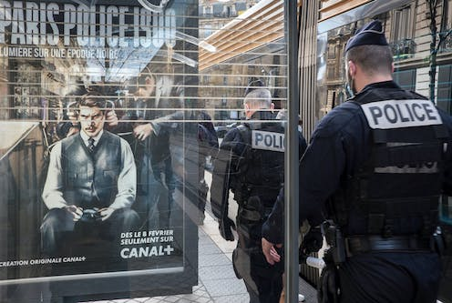 Police walk past a bus shelter with an add for a police cop show