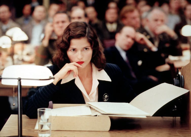 Woman on TV show sits in a court room with a large book open in front of her.