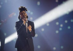 The Weeknd sings in front of a crowd.