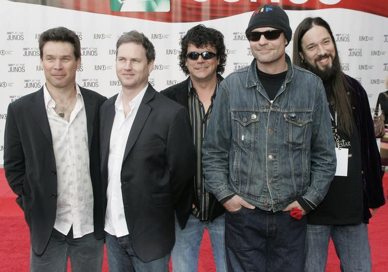 Members of The Tragically Hip, including Gord Downie in a toque and sunglasses, pose for photographers on the red carpet
