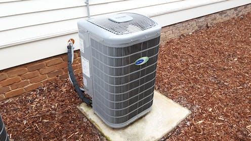 Air source heat pump on a concrete pad outside a home.