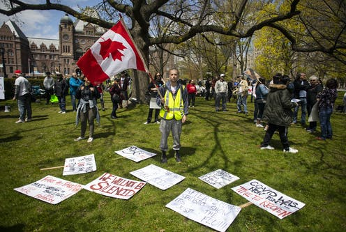 (Man stands holding an upside down Canada flag with COVID misinformation signs around him reading things like 'we will not be silenced'