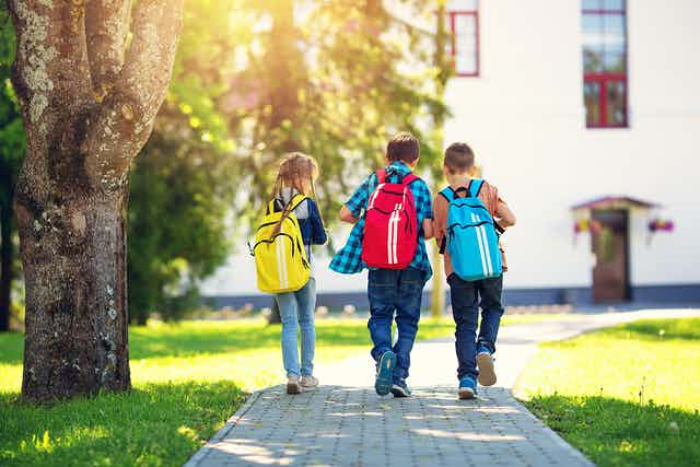 Kids walking to school with green space around them.