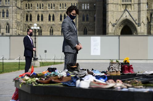 Justin Trudeau, wearing a suit and a black face mask, bows his head as he looks at shoes and flowers left at the Eternal Flame on Parliament Hill