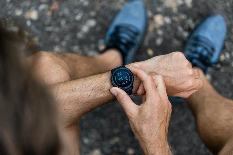 A man adjusts his smartwatch.