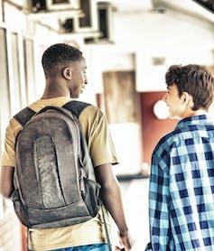 Two boys walking in a school corridor.