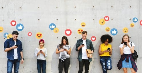 A row of people standing agains a wall with happy emoji icons floating over their heads