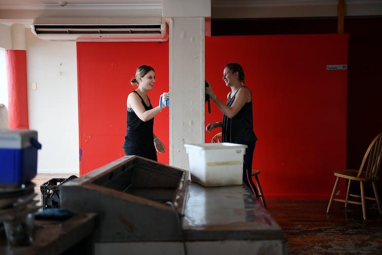 Two women wipe walls