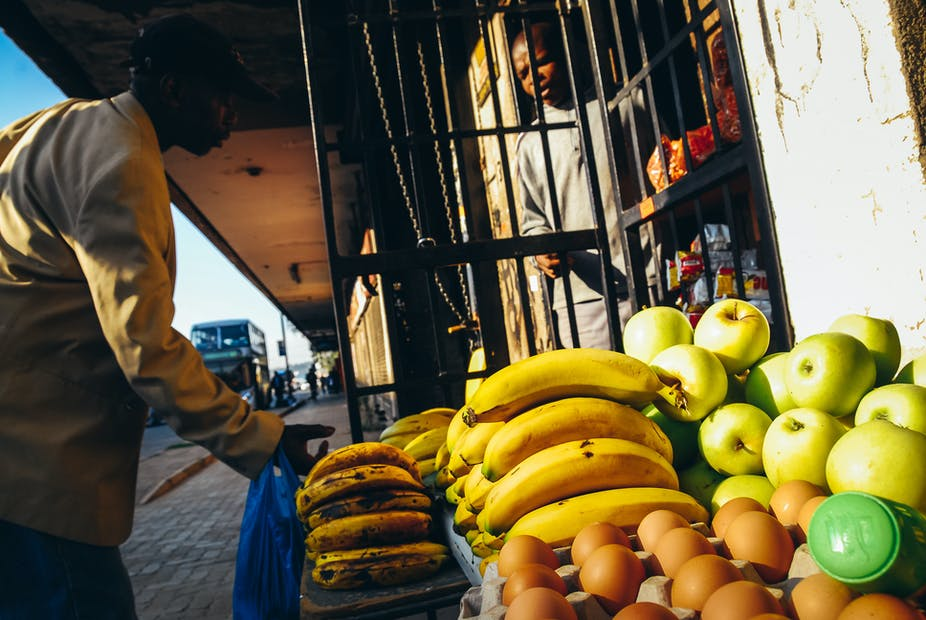 Customer at a pavement stall where fruit and eggs are on display