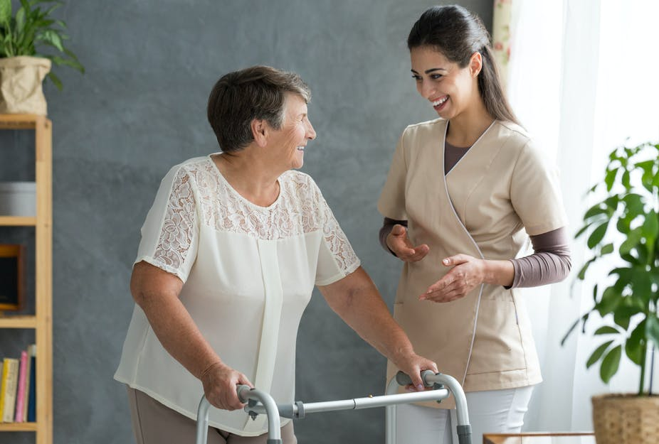 A woman standing with a zimmer frame next to a woman in scrubs.
