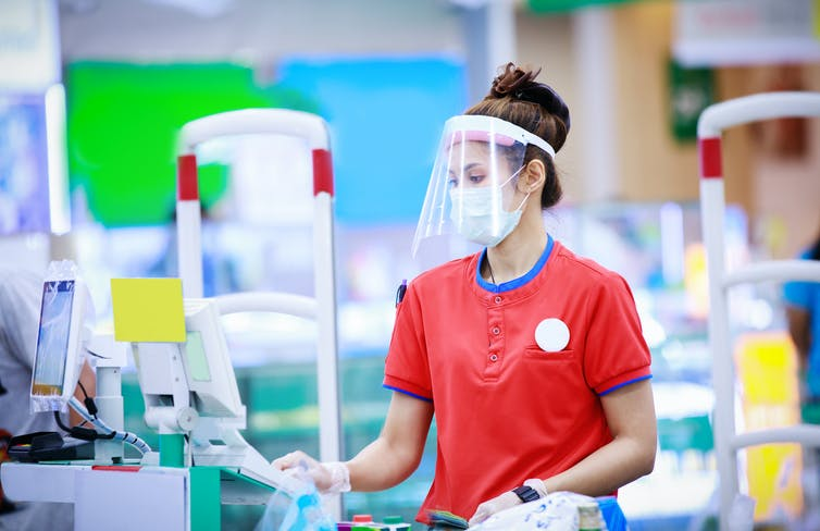 A female grocery store cashier wearing a face mask and shield.