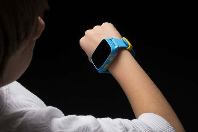 A child looking at a smart watch