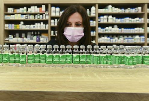Une femme portant un masque examine des fioles
