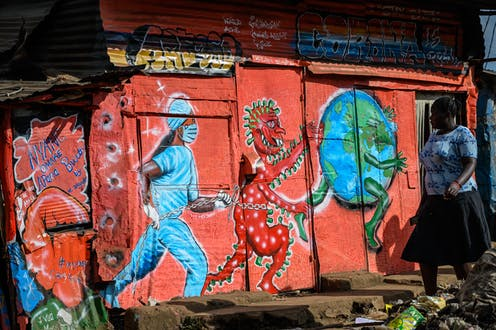 A woman walks past a mural painted on a shanty dwelling. It depicts a masked nose run-in after a devilish red virus, who is in turn running after the planet.