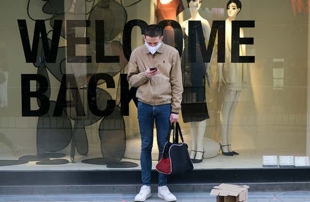 A man standing in front of a WELCOME BACK sign in a storefront window, wearing a face mask and holding a bag.