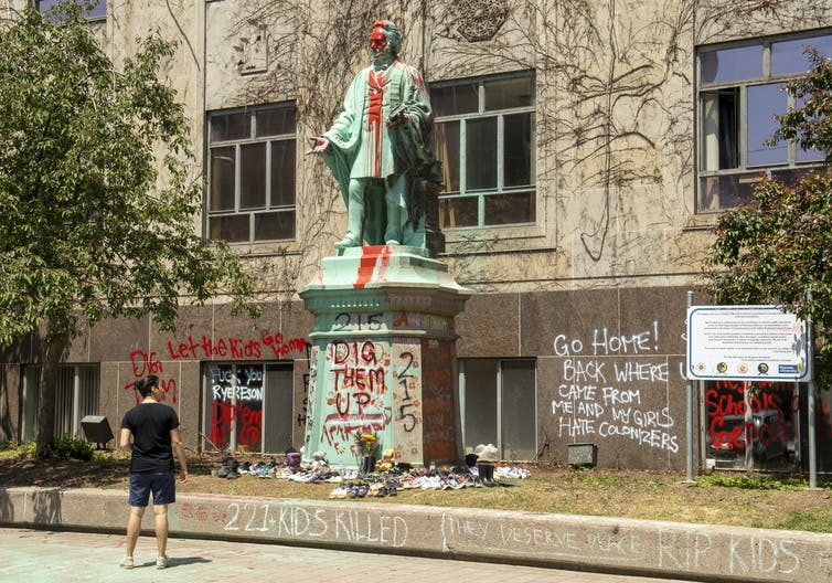 A woman looks at a spraypainted statue of Egerton Ryerson.
