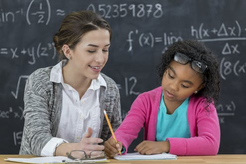 A teacher and student work together on an assignment.